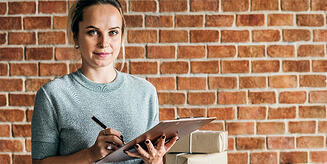 woman managing deliveries with clip board